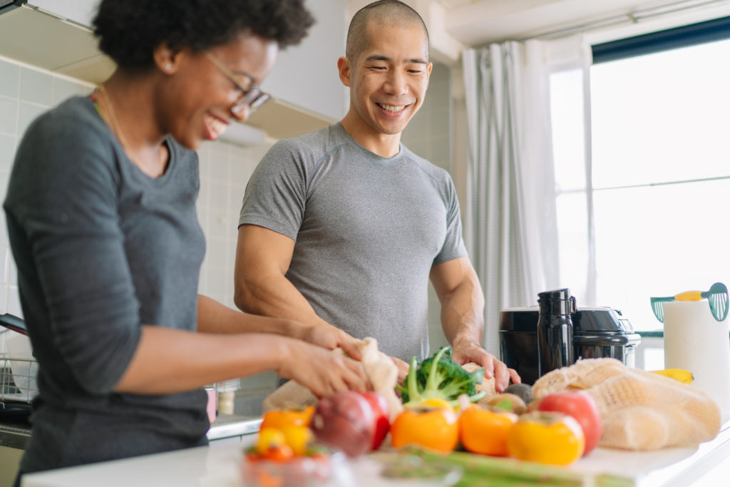 A young multi-ethnic couple is preparing vegan food in the kitchen at home.